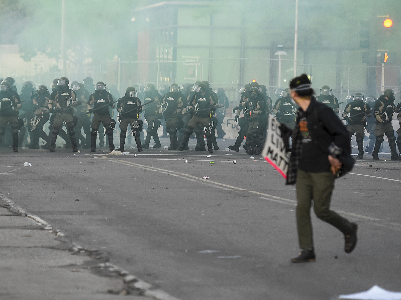 A man walking away from a line of police in riot gear