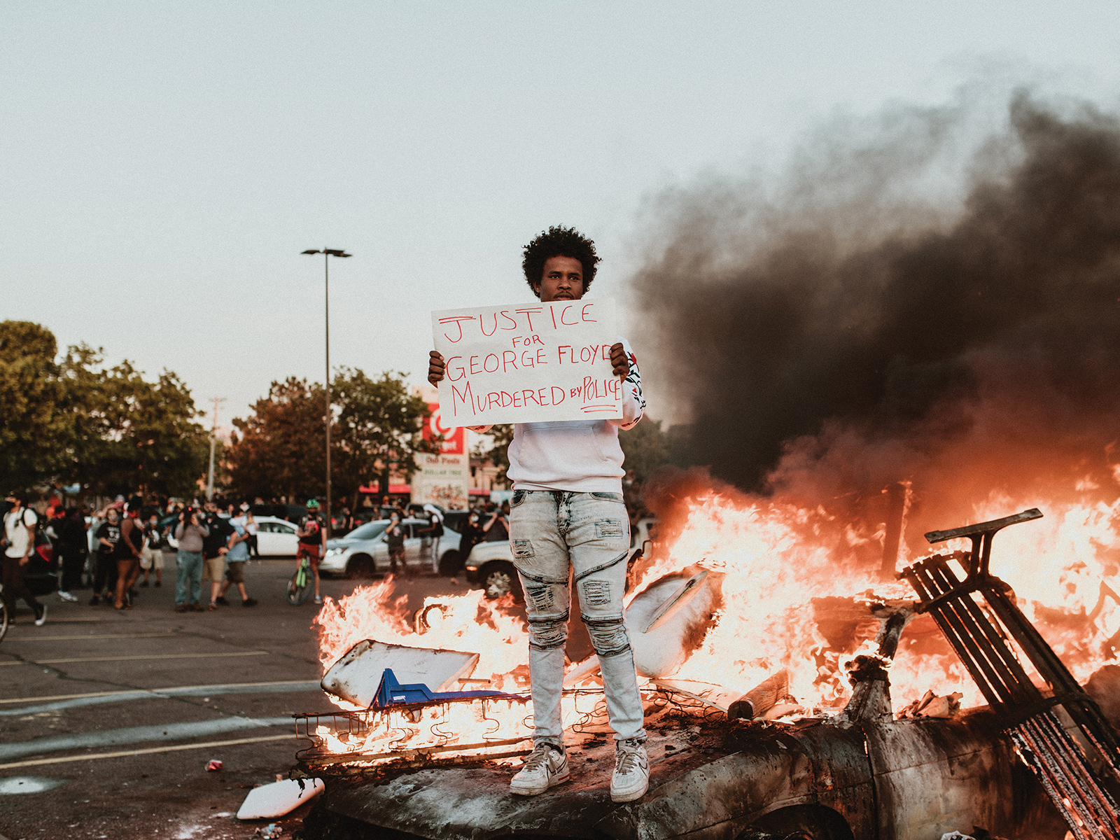 a man standing with a protest sign in front of a blazing fire