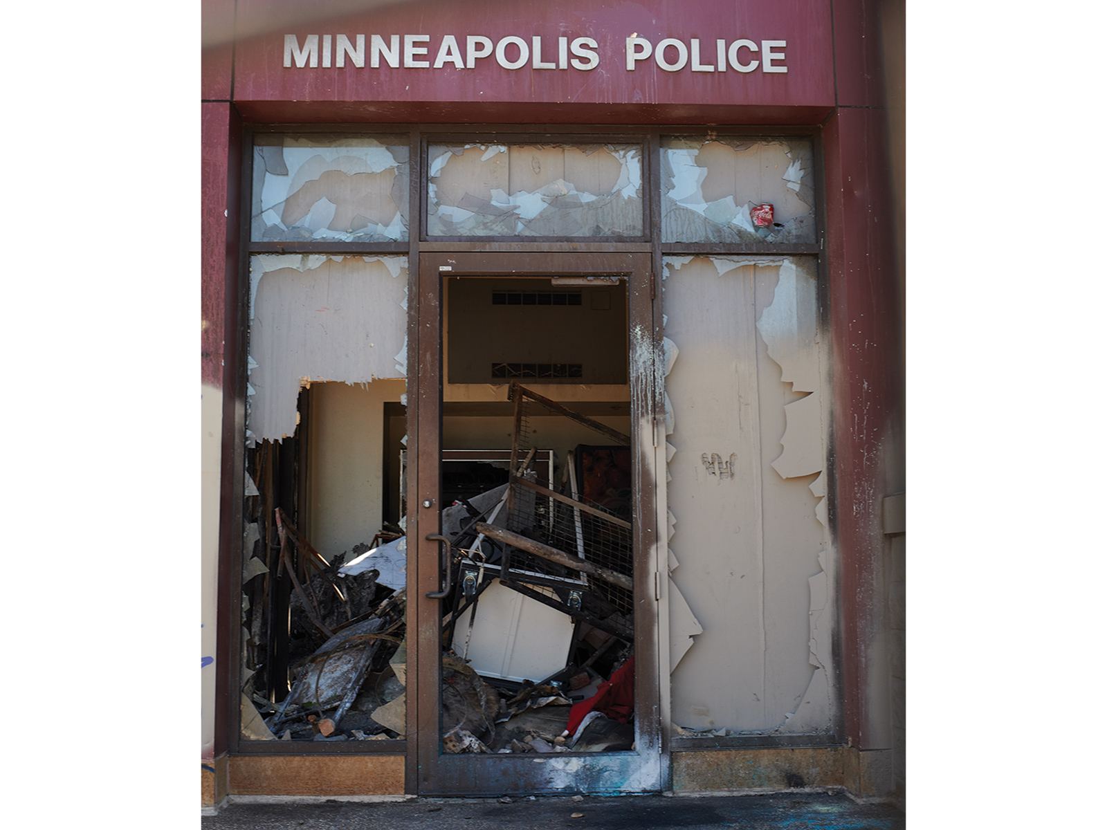 Entrance of a Minneapolis Police Station with the windows broken and rubble in the entryway