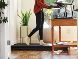 Woman walking on a treadmill at a workstation