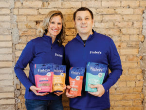 Angie and Kyle Gallus holding bags of their dog treats