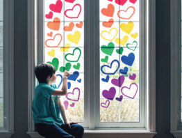 child putting hearts of rainbow colors on window