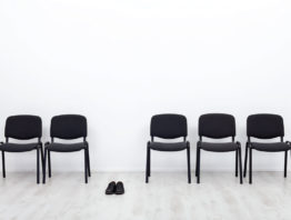 Four black chairs and a pair of black shoes