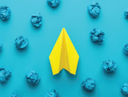 yellow paper airplane with crumpled up blue paper and blue background